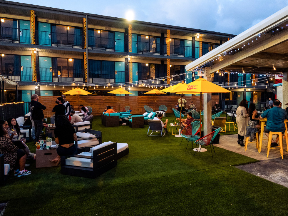 an outdoor grassy lounge area with lots of seating and people, large yellow umbrellas, and a covered patio