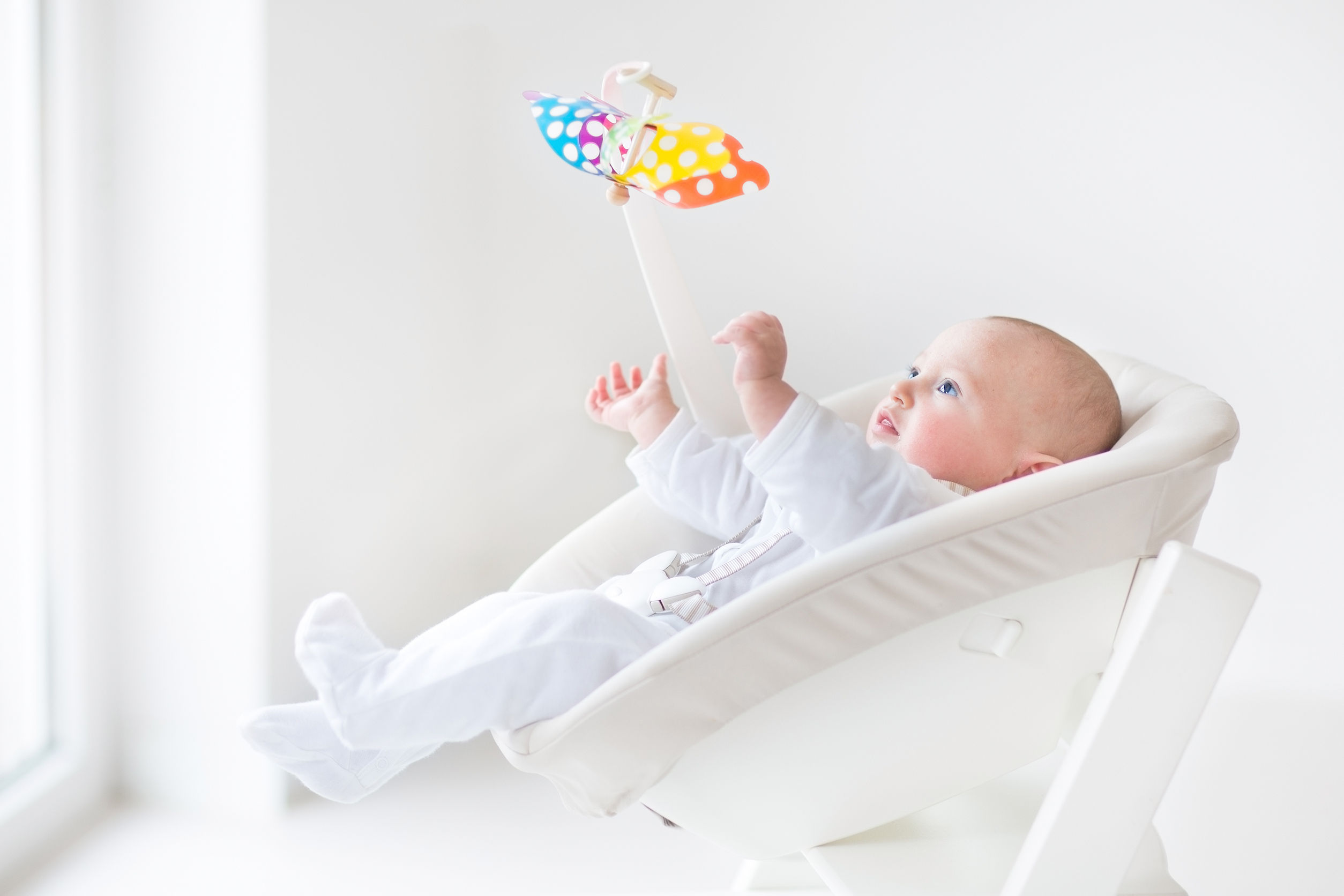 30780455 - cute newborn baby boy watching a colorful mobile toy sitting in a white high chair next to a window