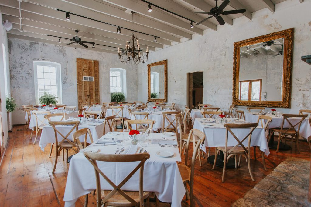 a rustic restaurant room with large mirrors on the wall, a chandelier, several empty, small tables with white tablecloths and full place settings, big windows, and wooden floors