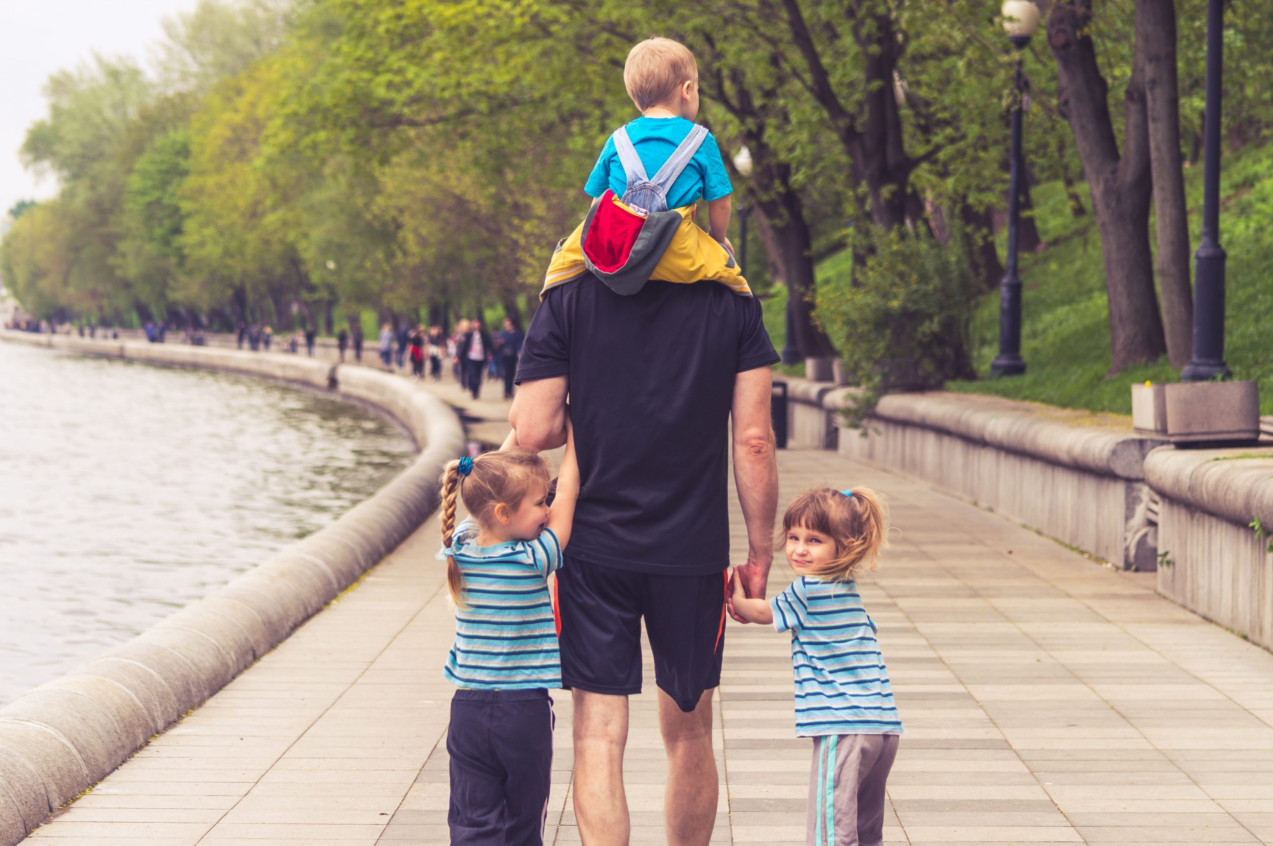 Man with a kid on his shoulders, holding hands with two kids, walking down a riverwalk